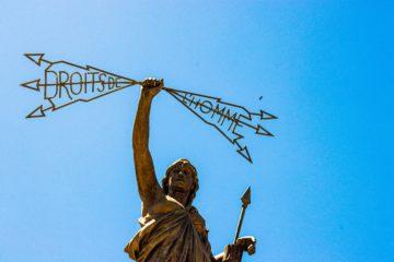 """Statue, die Pfeile hochhält mit der französischen Schrift """"Droits de l'homme"""" (Menschenrecht)"""