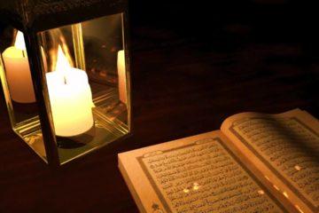 Arabischer Koran mit einer leuchtenden Kerze nebendran