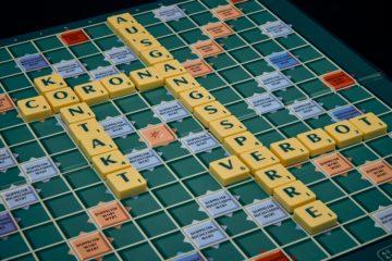 Scrabble-Brett mit Corona, Kontakt, Ausgangssperre und Verbot als zusammengesetzte Wörter