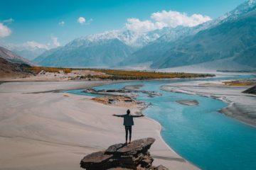 Mann steht vor riesiger Landschaft, genießt Freiheit und Selbstbestimmung