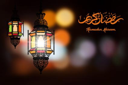 Ramadan Kareem Gruss in handgezeichneter Kalligrafie vor verschwommenem Hintergrund mit schöner Beleuchtung mittels einer arabischen Lampe. Vektor-Illustration.