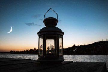 Mondsichel im Hintergrund zu Dämmerungszeiten mit einer Glühlampe im Vordergrund