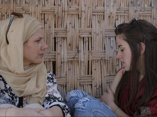 Zwei Frauen, eine bedeckt, eine mit offenem Haar, schauen nachdenklich.