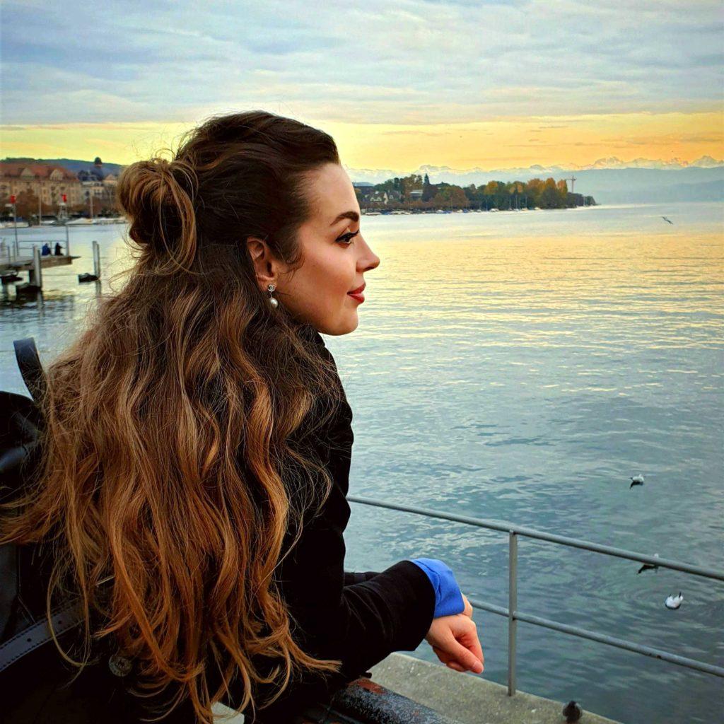 Vorstandsmitlgied Ajsa Schenkel blickt am Seeufer zum See hinaus, im Hintergrund ein Sonnenuntergang mit Wolken